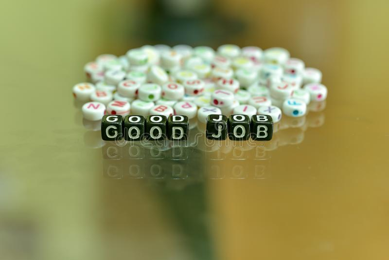GOOD JOB written with Acrylic Black cube with white Alphabet Beads on the Glass Background.  stock image