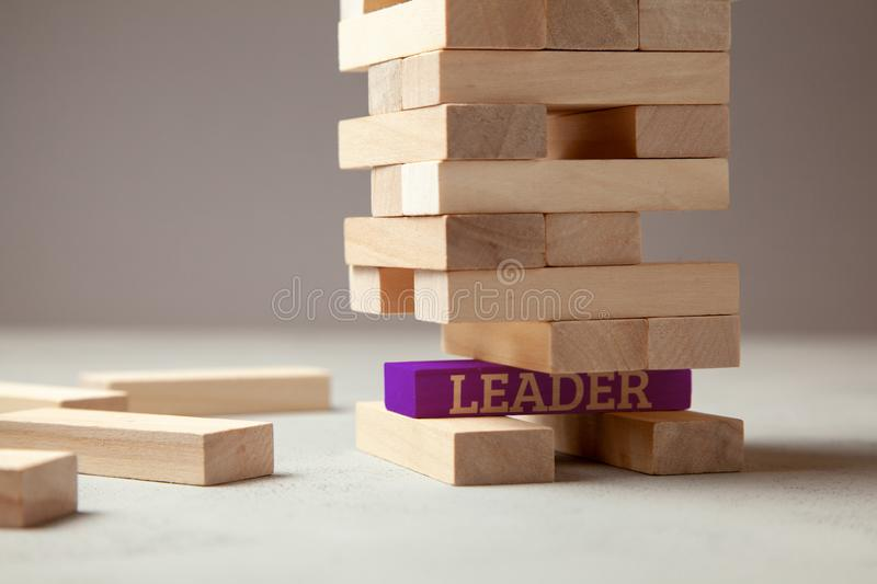 Good leader is building successful team and company in business. Tower of wooden blocks with the inscription leader royalty free stock photo