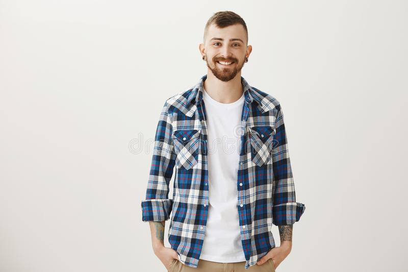 Good-looing confident adult boyfriend with flesh-tunnels and beard standing in blue plaid shirt over gray background royalty free stock photo