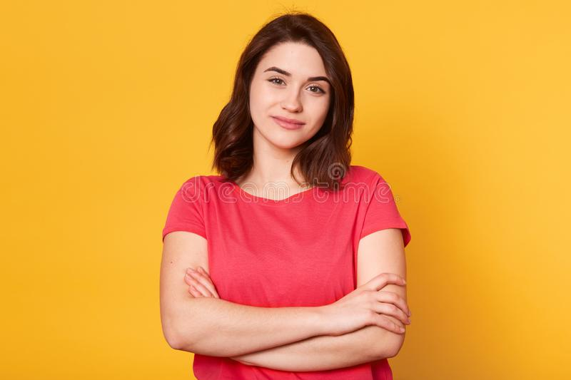Good looking adorable young woman looking directly at camera, having pleasant facial expression, having short black hair, standing royalty free stock images