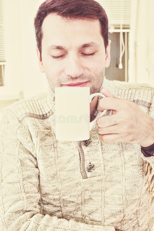Good looking adult man savouring the aroma of a cup of fresh hot stock photo