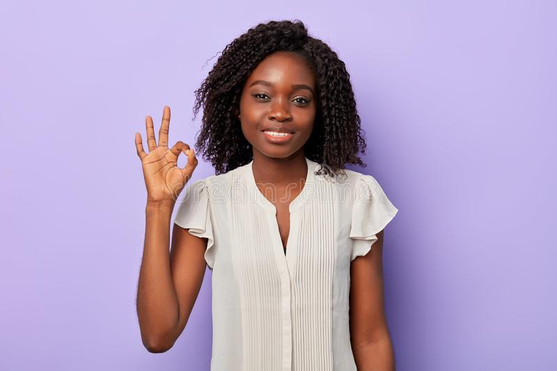 Good looking american woman in white shirt showing ok with fingers. royalty free stock photography