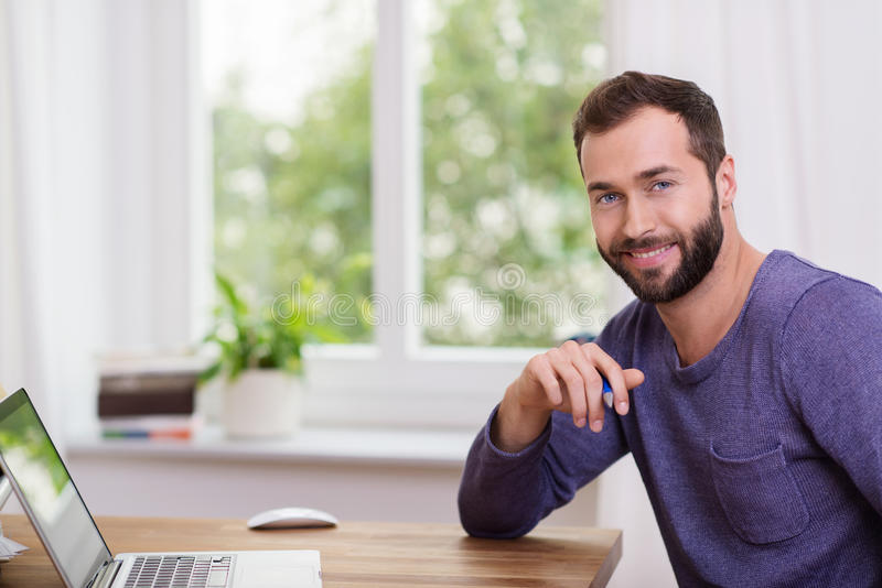 Good-looking bearded man in a home office royalty free stock images