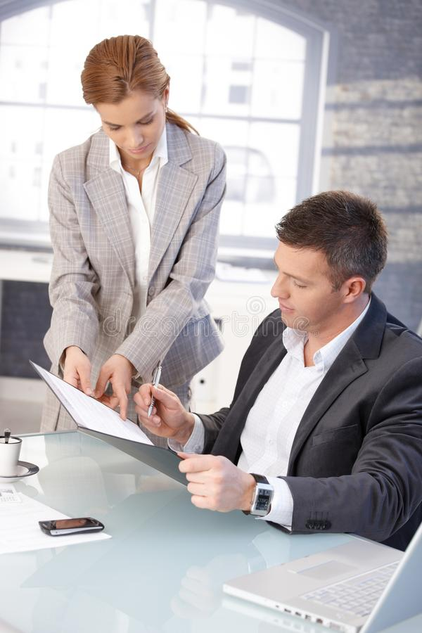 Good-looking boss signing contract at desk stock images