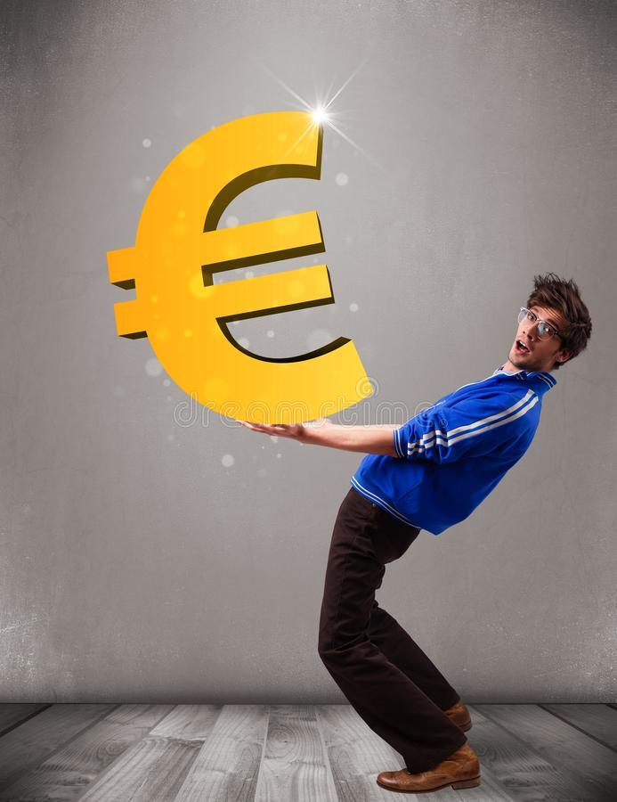 Good-looking boy holding a big 3d gold euro sign stock photography