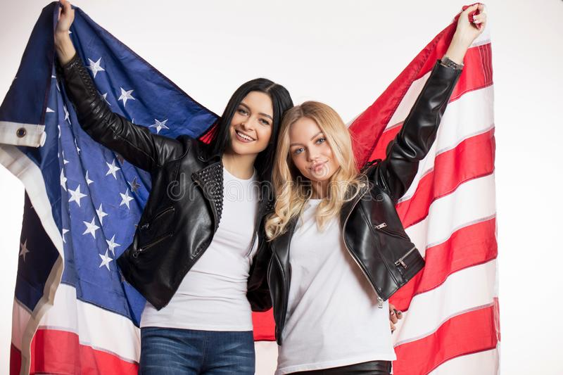 Good looking brunette and blonde are holding the USA flag stock photos