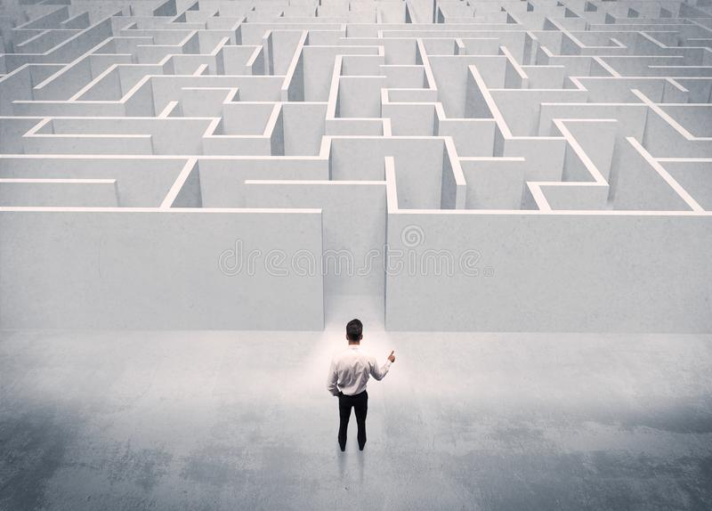 Sales person standing at maze entrance. A good looking businessman standing in front of white labirynth entrance about to make a decision concept royalty free stock photos