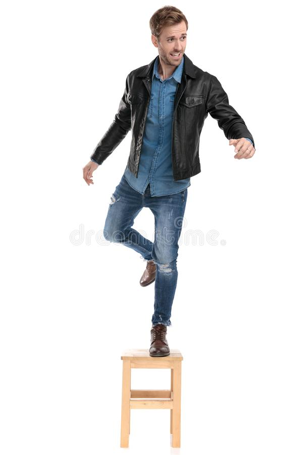 Man maintaining his balance fooling around. Good looking casual man with black leather jacket is standing in one foot on a chair and the other raised fooling stock image