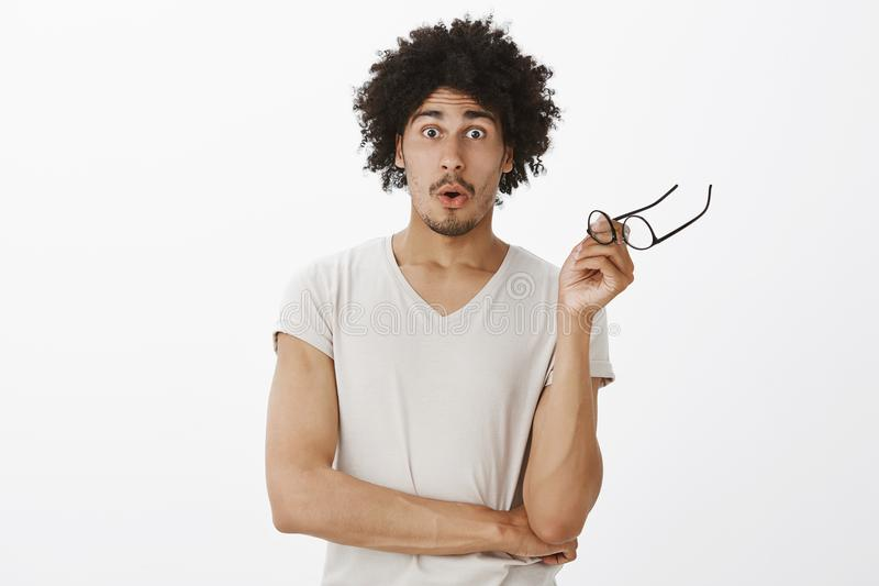 Good-looking charming man with beard and afro haircut, holding glasses and folding lips, gazing with popped eyes at stock photography