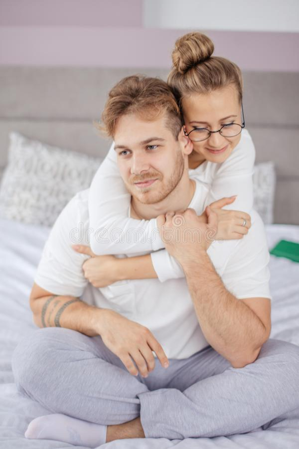 Good looking couple embraces passionately, sits on comfortable bed royalty free stock images