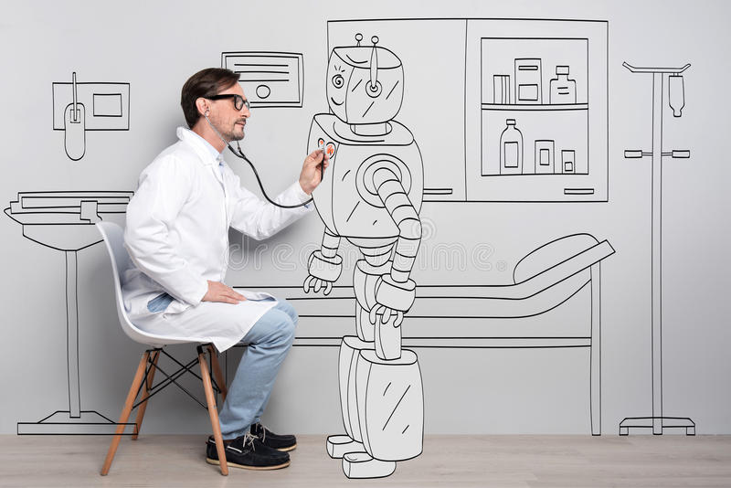 Good looking doctor examine robots heart. royalty free stock photos