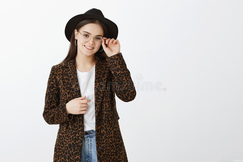 Good-looking fashionable european girl in glasses, hat and coat with leopard print, touching rim of eyewear and smiling. Broadly, going shopping for new clothes royalty free stock photos