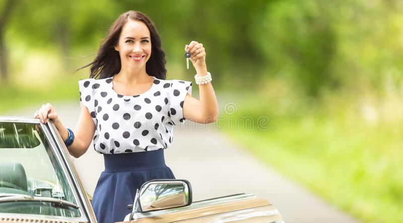 Good-looking girl smiling holds car keys from a rented cabriolet royalty free stock photos