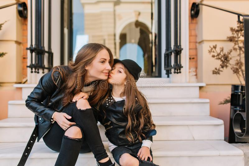 Good-looking girl in stylish black jeans kissing her little sister, sitting on the stairs of shop. Outdoor portrait of. Young brown-haired women resting with royalty free stock photos