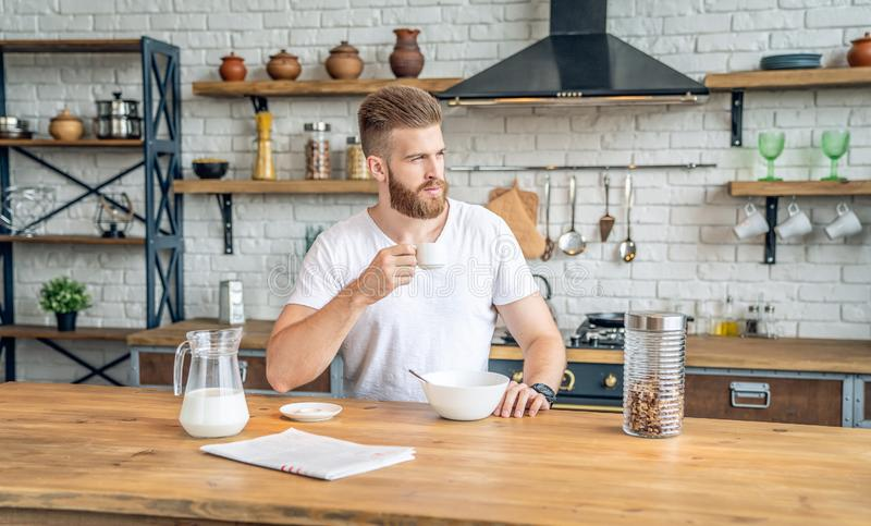 Good looking handsome bearded man is sitting in the kitchen drinking morning coffee with cereals and milk. reading morning press, stock images