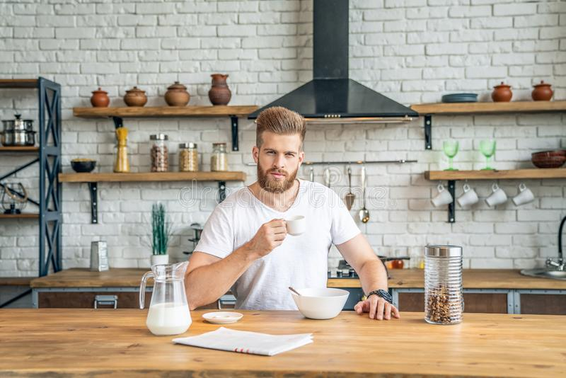 Good looking handsome bearded man is sitting in the kitchen drinking morning coffee with cereals and milk. reading morning press, royalty free stock photos