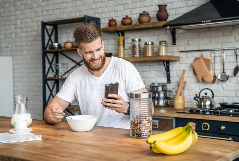 Good looking handsome bearded man is sitting in the kitchen having breakfast cereals and milk, coffee and bananas. checking his stock photos