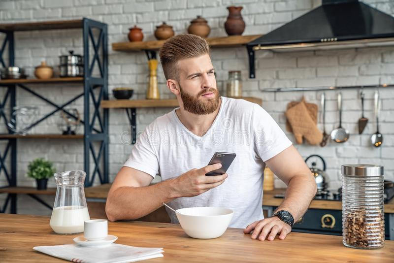 Good looking handsome bearded man is sitting in the kitchen having breakfast cereals and milk, coffee and bananas. holding his stock images