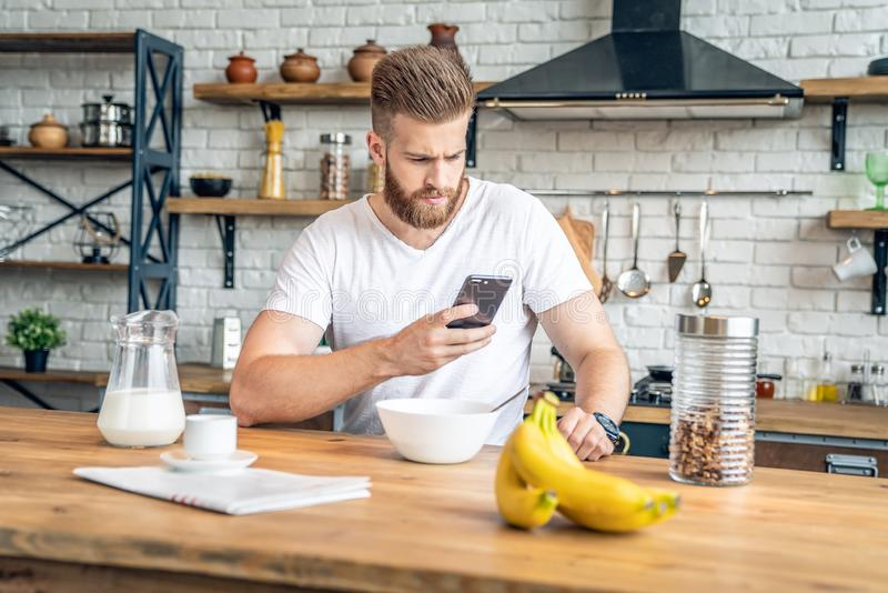 Good looking handsome bearded man is sitting in the kitchen having breakfast cereals and milk, coffee and bananas. reading morning royalty free stock photography