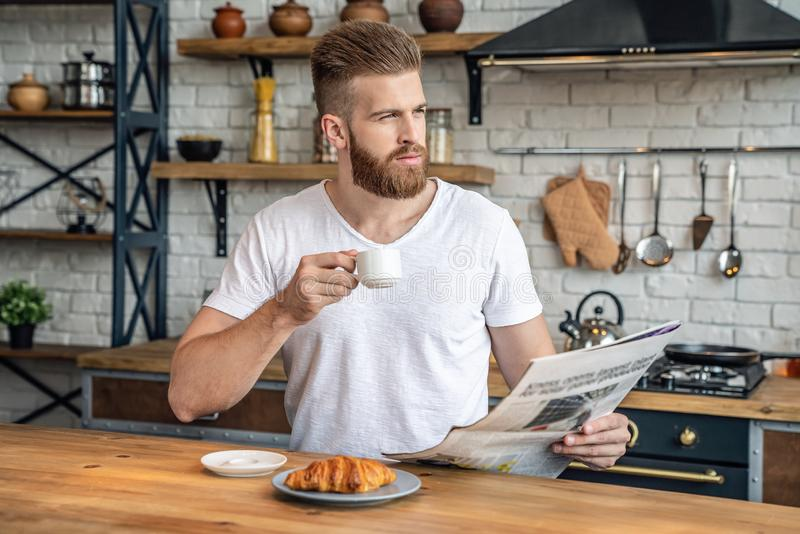 Good looking handsome bearded man is taking a rest sitting in the kitchen in the morning eating croissant with coffee, reading royalty free stock image