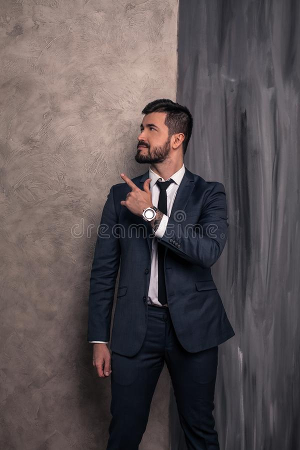 Good looking handsome businessman is standing in his office pointing fingers to the side. wearing suit and a tie stock photo