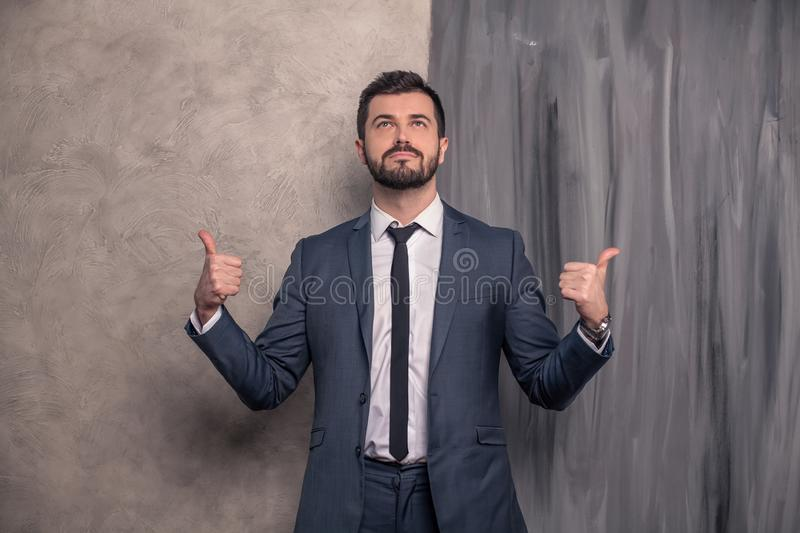 Good looking handsome businessman is standing in his office pointing fingers to the sides and looking up. wearing suit and a tie stock images