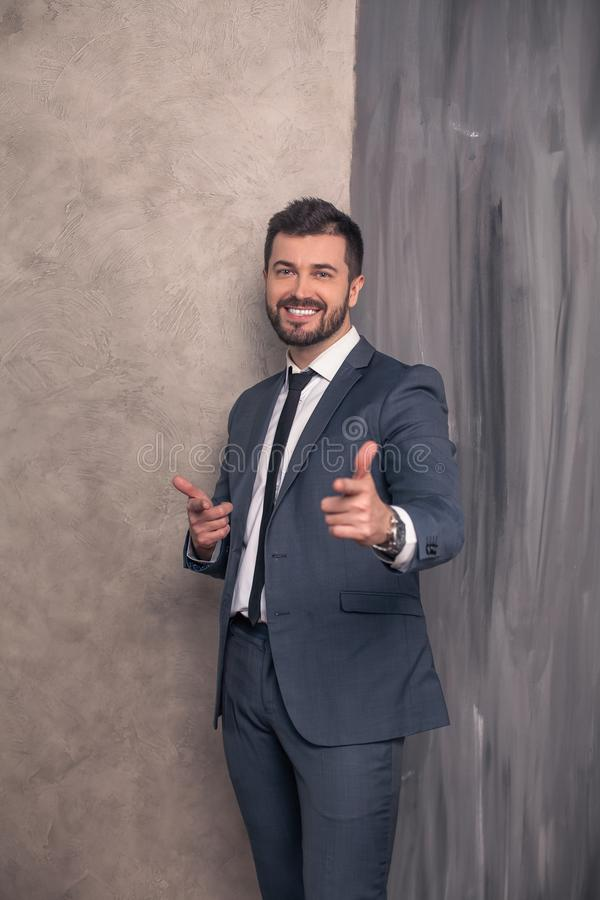Good looking handsome happy businessman is standing in his office pointing fingers to the camera and smiling. wearing suit and a stock photo