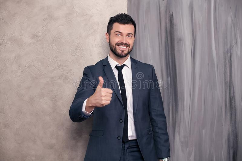 Good looking handsome happy businessman is standing in his office showing cool sigh and smiling. wearing suit and a tie royalty free stock image