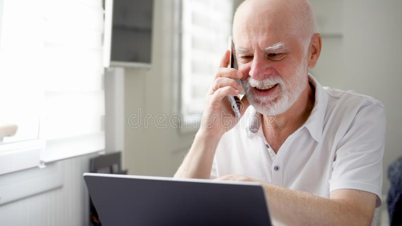 Senior man sitting at home with laptop and smartphone. Using cellphone discussing project on screen royalty free stock image