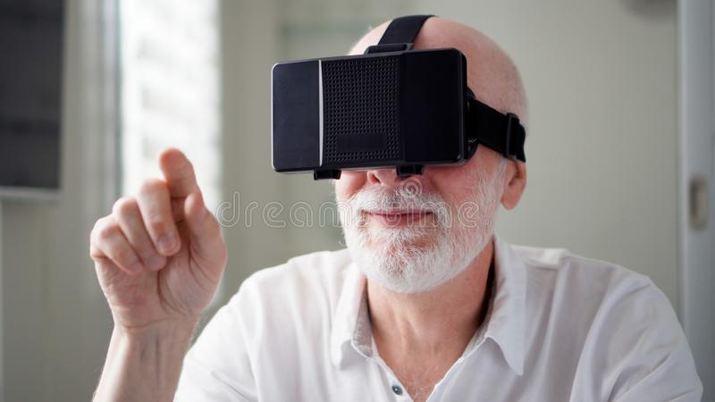 Handsome senior man in white using VR 360 glasses at home. Making browse and tap gestures royalty free stock photo