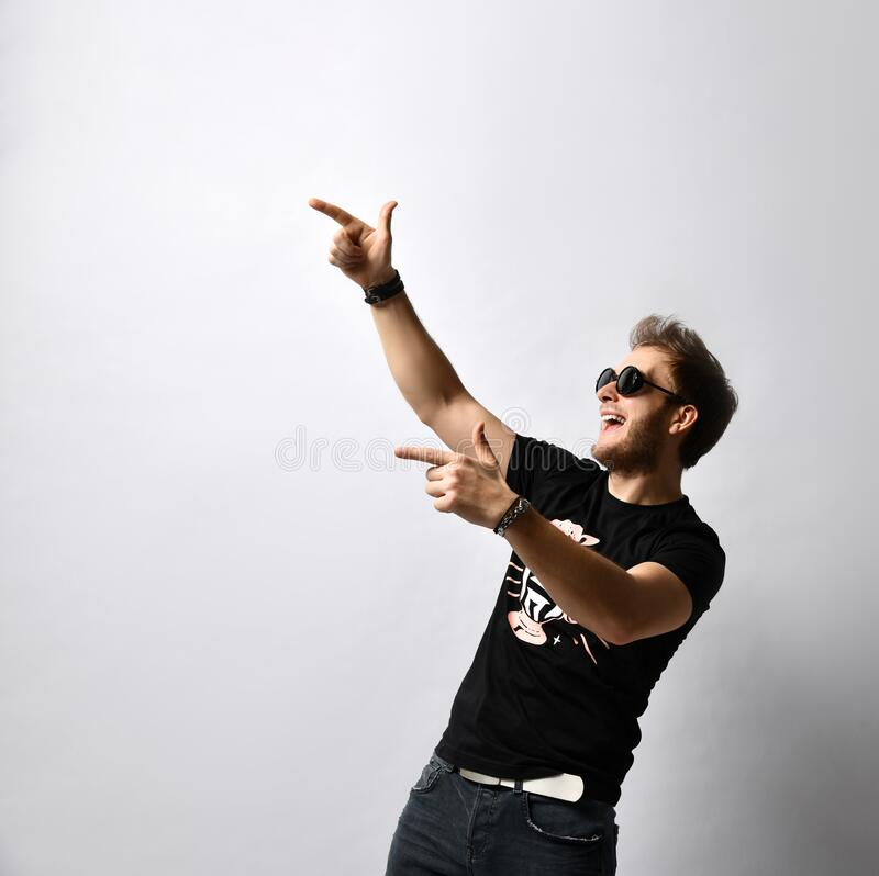 Hipster fellow in sunglasses, black t-shirt with print, bracelets. He is pointing at someone, posing isolated on white. Close up. Good-looking hipster fellow stock image
