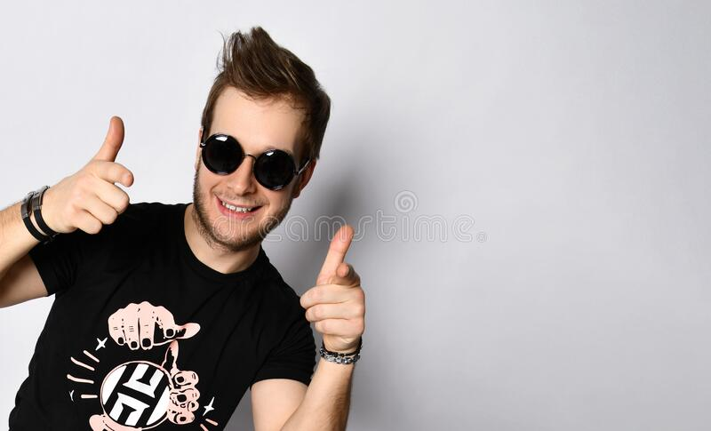 Male in sunglasses, black t-shirt, bracelets, jeans and sneakers. Smiling, showing thumbs up posing isolated on white. Full length. Good-looking hipster male in stock photo