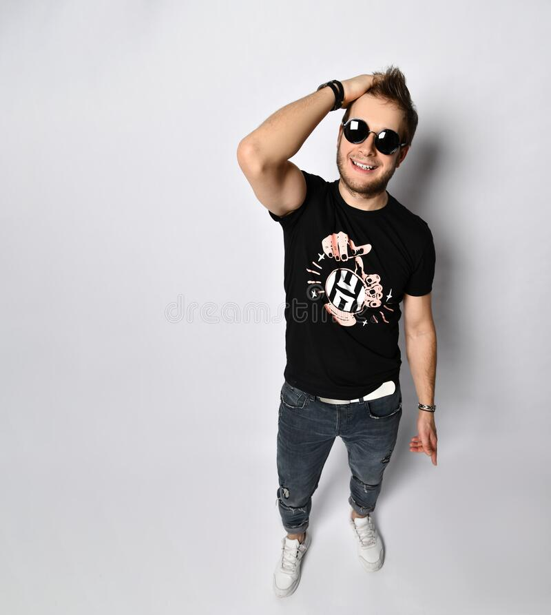Male in sunglasses, black t-shirt, bracelets, jeans and sneakers. Smiling, showing thumbs up posing isolated on white. Full length. Good-looking hipster male in royalty free stock image