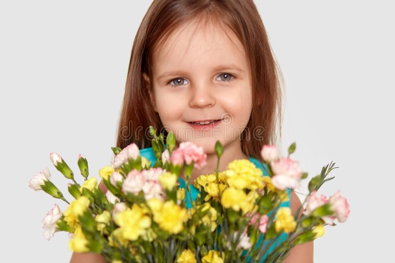 Good looking little kid with charming smile, holds flowers, has pleased facial expression, enjoys nice day, isolated over white stock photography