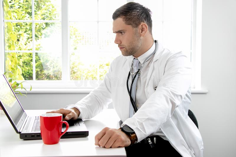 Good looking male doctor in white lab coat gp at desk looking at laptop computer stock photos