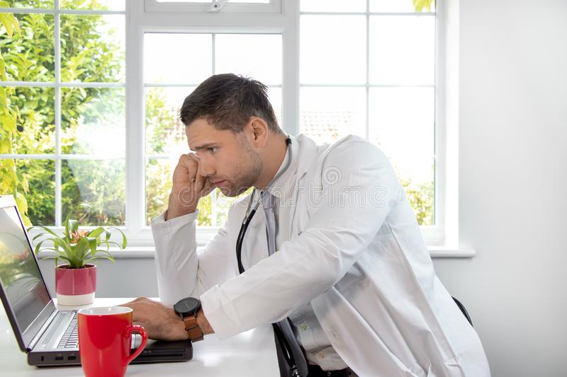 Good looking male doctor in white lab coat gp at desk looking at laptop computer royalty free stock photo
