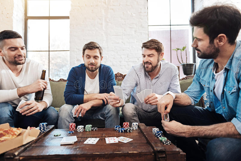 Good looking male friends playing poker royalty free stock photography
