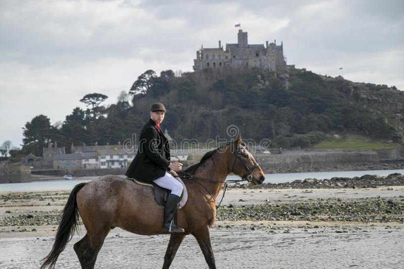 Good Looking Male Horse Rider riding horse on beach in traditional riding clothing with St Michael`s Mount in background stock photos