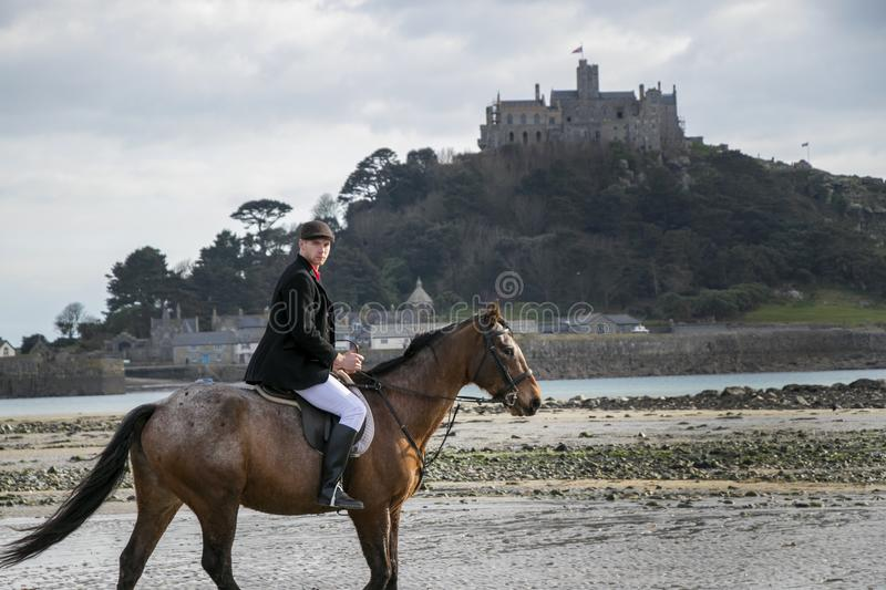 Good Looking Male Horse Rider riding horse on beach in traditional riding clothing with St Michael`s Mount in background stock image
