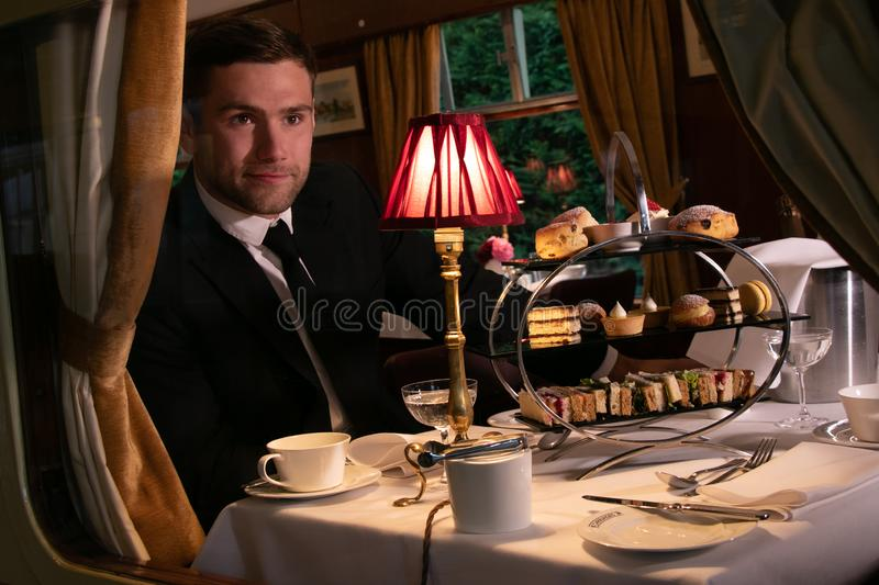Good looking man in suit enjoying afternoon tea in vintage train carriage. Handsome man in black suit sitting in vintage train carriage enjoying afternoon tea stock photos