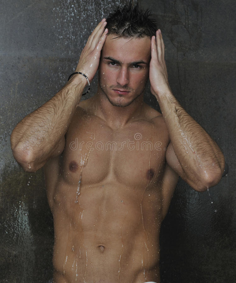 Good looking man under man shower. Young good looking and attractive man with muscular body wet taking showr in bath with black tiles in background stock images