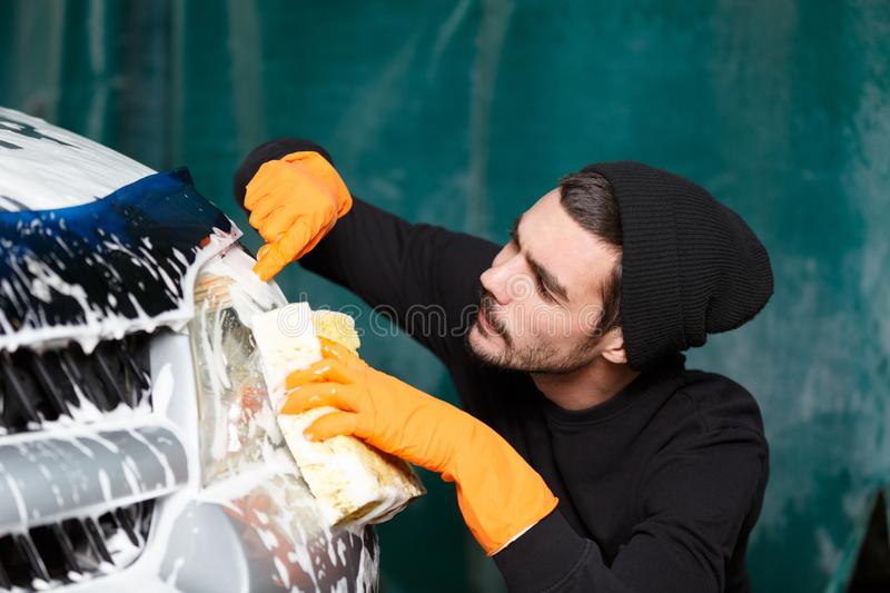 A good-looking man washes a bumper royalty free stock photo