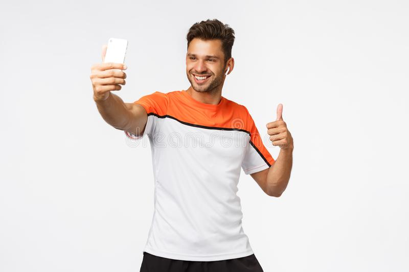 Good-looking masculine young sportsman wear wireless earphones, activewear, taking selfie on smartphone, show thumb-up stock images