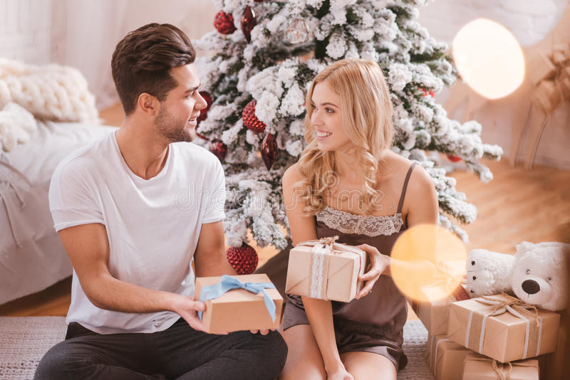 Good looking nice couple exchanging their Christmas presents stock image