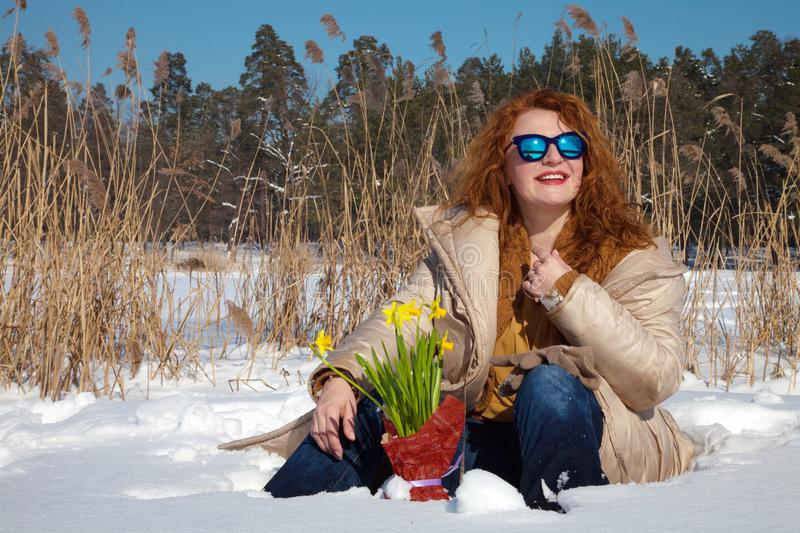 Good looking optimistic woman admiring winter weather while sitting in snow. Gorgeous middle aged woman with wavy red hair and sunglasses admiring winter weather royalty free stock photos