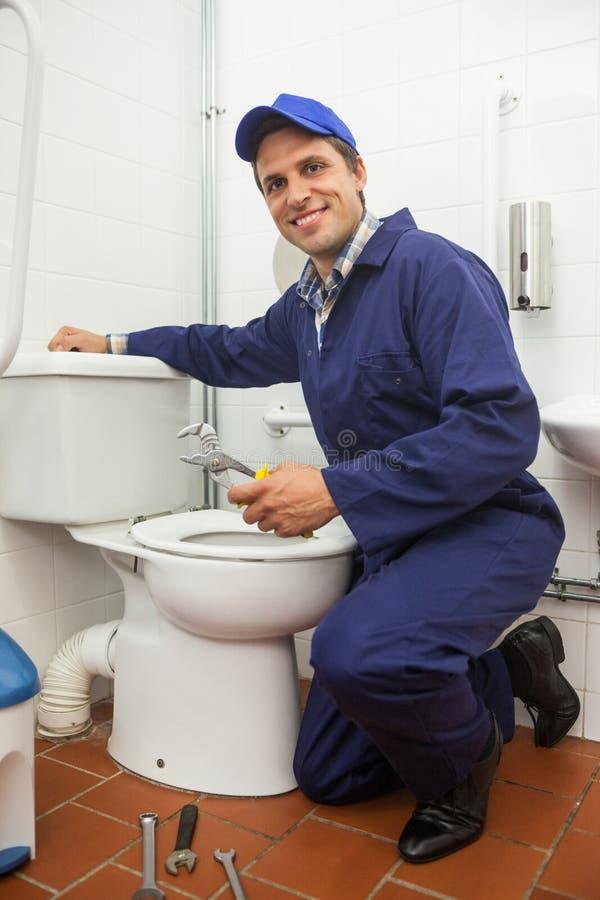 Good looking plumber repairing toilet stock photos