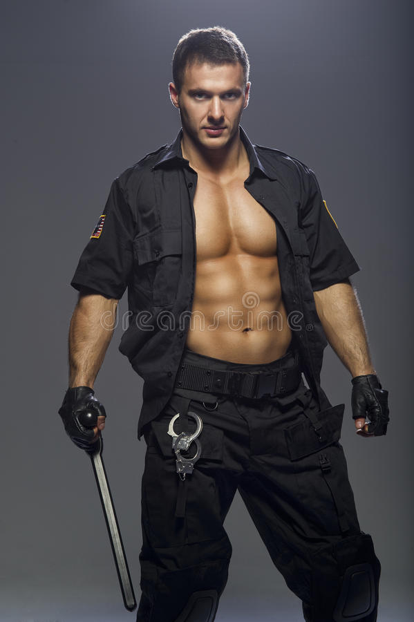 Good looking policeman bodybuilder posing royalty free stock photo