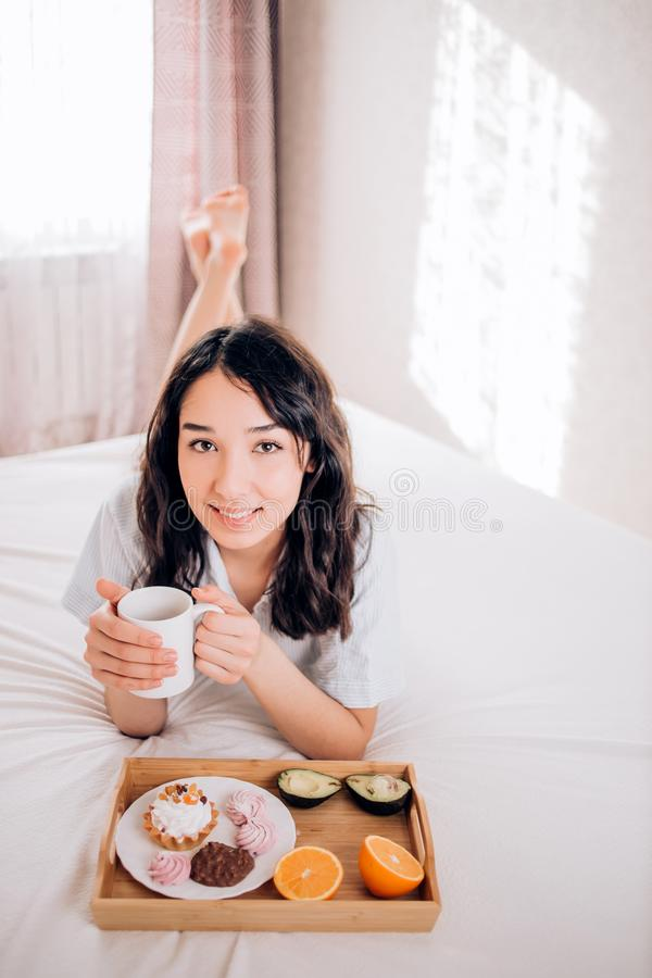Young woman eating healthy breakfast in bed royalty free stock photo