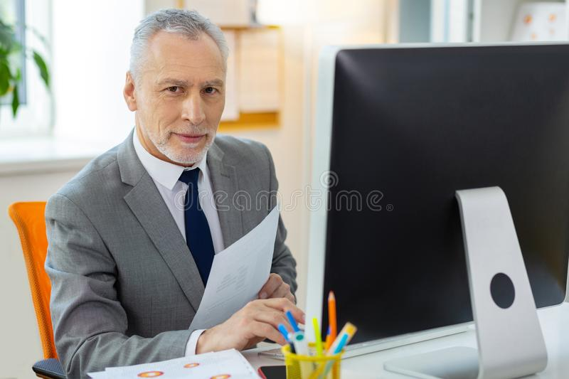 Good-looking senior office worker inspecting papers and computer information stock photo
