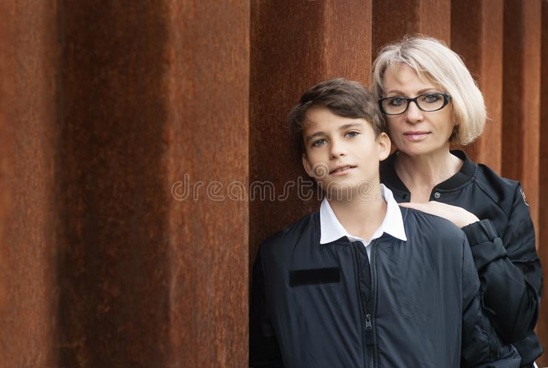 Good-looking, single-parent mom and teen son in the park. Photo. With copy space. Cohesion, friendship and family relations royalty free stock image